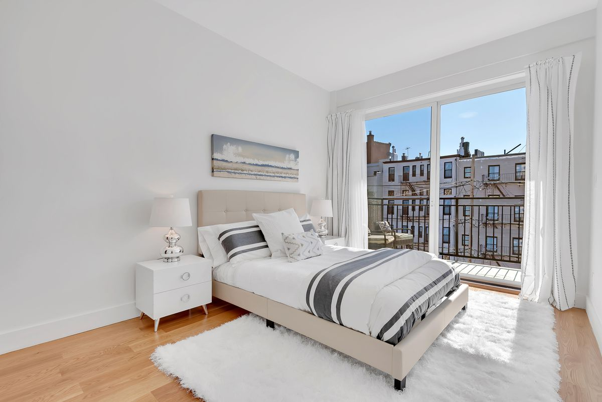 A bedroom with light grey walls, a glass door that leads to a balcony, and a white rug.