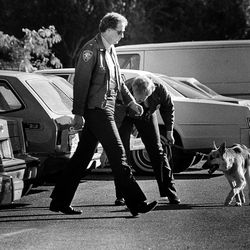 .Officers and a dog check a parking lot during the Tuesday, Oct. 18, 1985, funeral of Kathy Sheets, who died in bomb blast.