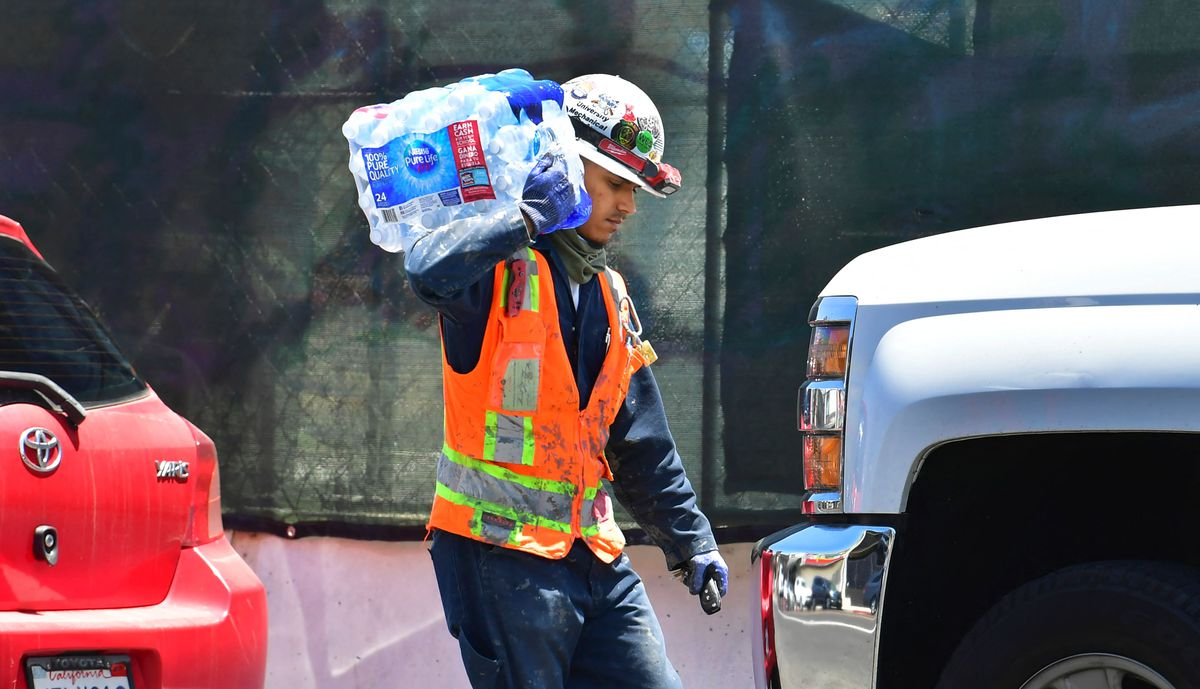 A construction worker carries a 24-pack of bottled water over his shoulder on June 14, 2021, in Los Angeles.