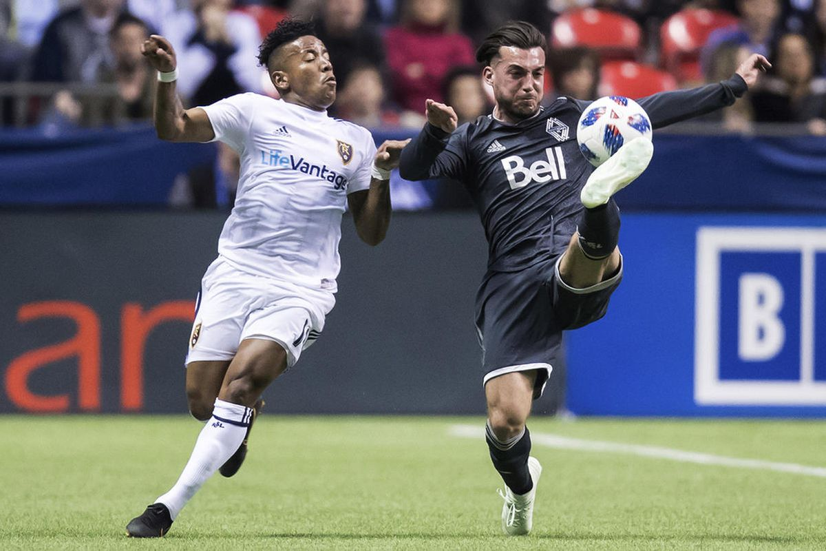 Vancouver Whitecaps' Russell Teibert, right, gets his foot on the ball in front of Real Salt Lake's Joao Plata during the first half of an MLS soccer match Friday, April 27, 2018, in Vancouver, British Columbia. (Darry Dyck/The Canadian Press via AP)