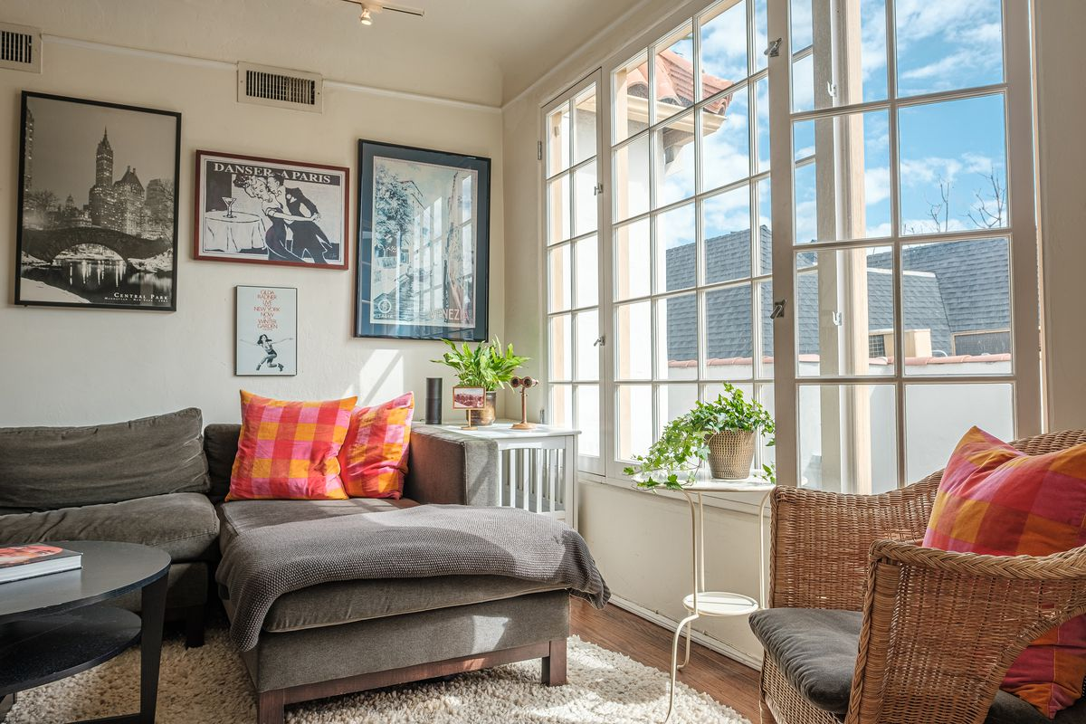 A view of the corner of the living room. The sun is shining through the wall of windows.