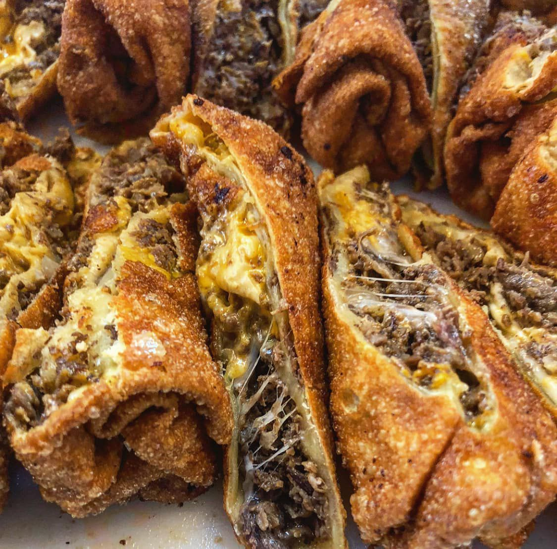 Two rolls of overly stuffed sliced beef cheesesteak egg rolls with gooey melted cheddar