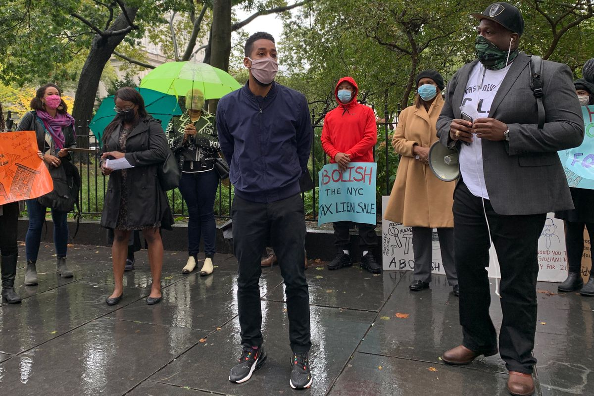 Council member Antonio Reynoso, left, and Al Scott, a homeowner and organizer with East New York Community Land Trust Initiative, speak outside City Hall during a rally demanding an end to the city's tax lien sales, October 13, 2020.