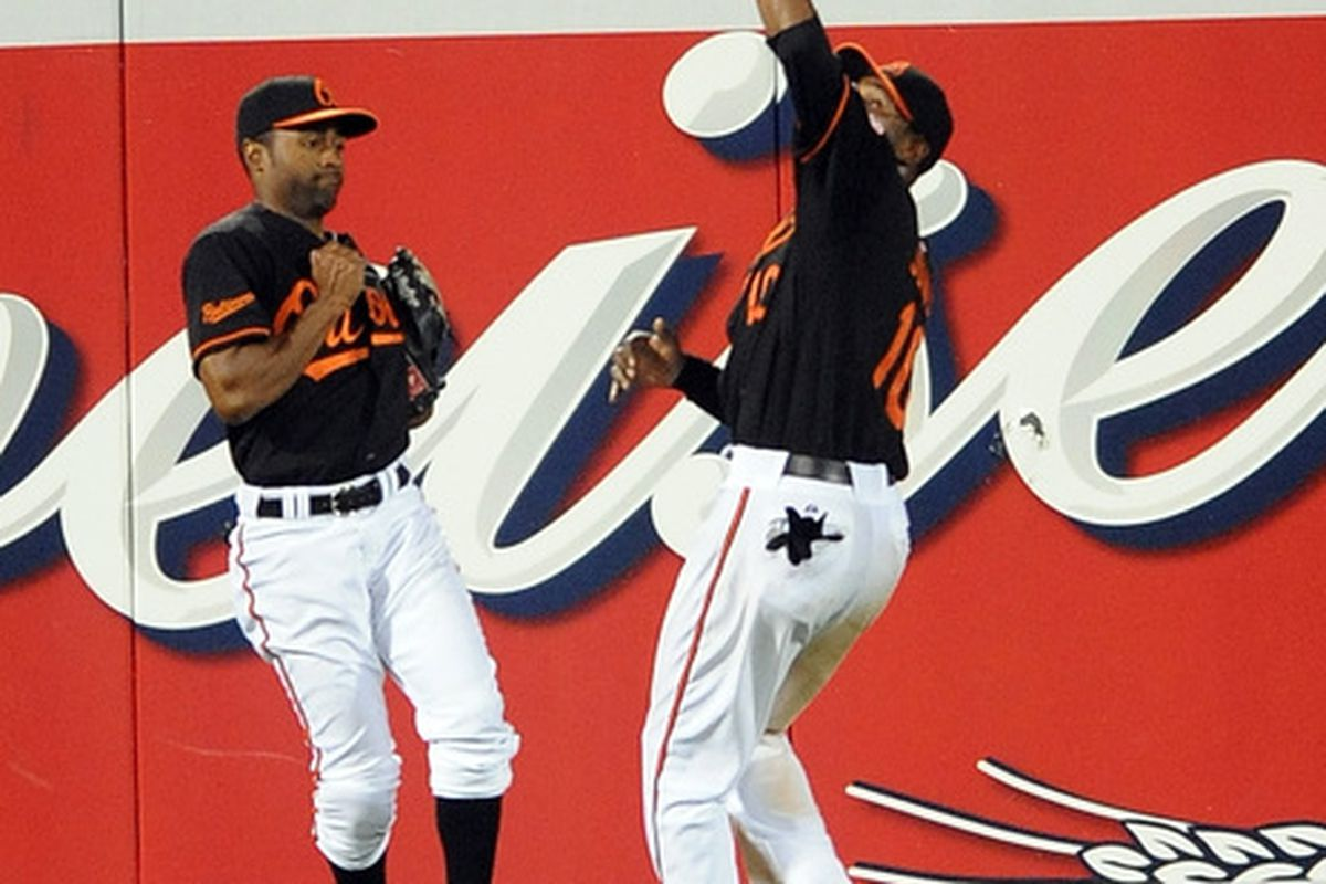 Adam Jones catches a fly ball in front of Corey Paterson. (Photo by Greg Fiume/Getty Images)