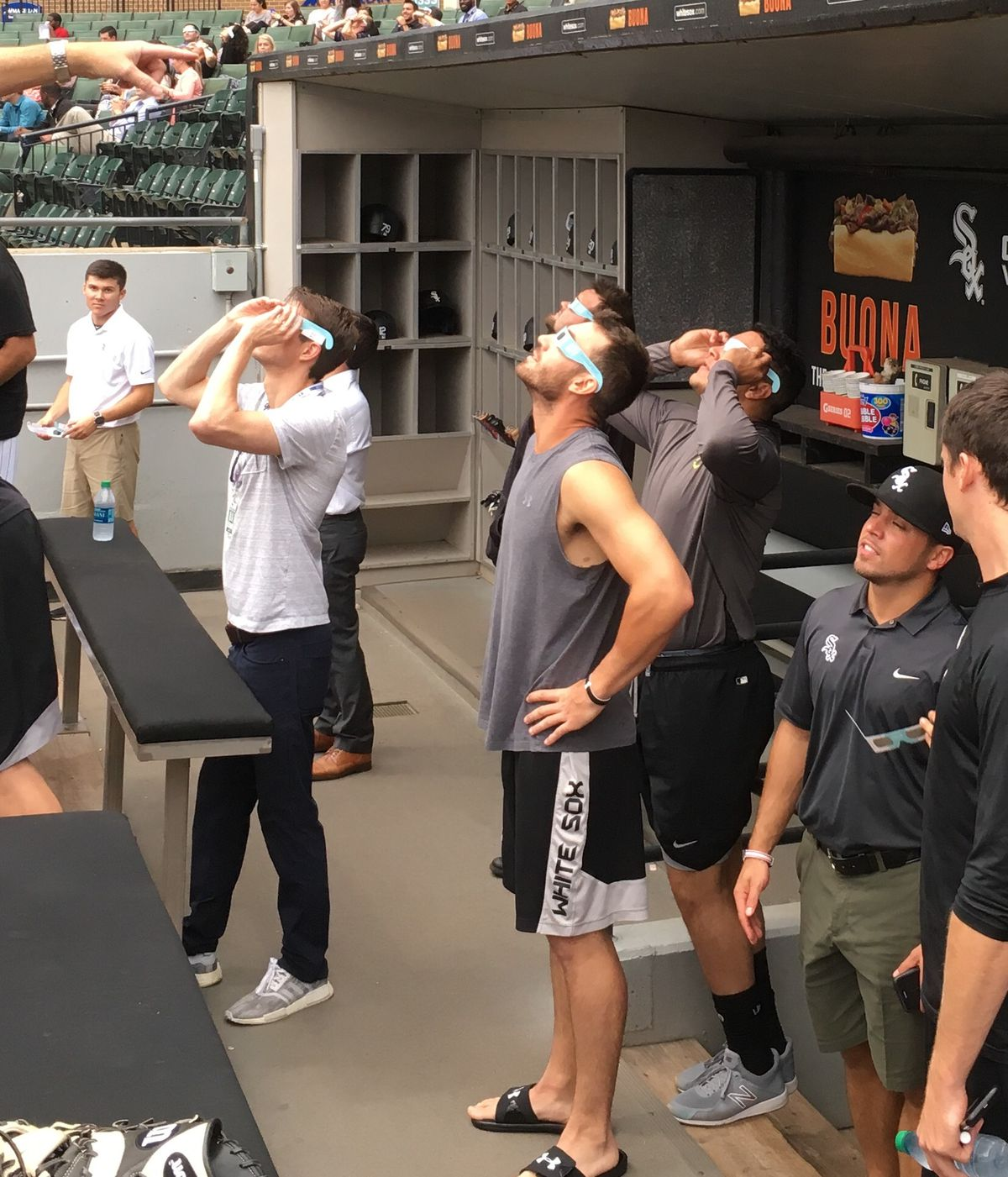 White Sox players, including Nicky Delmonico (middle) and Avisail Garcia, watch the eclipse from the dugout before Monday's games. (Photo by Daryl Van Schouwen)