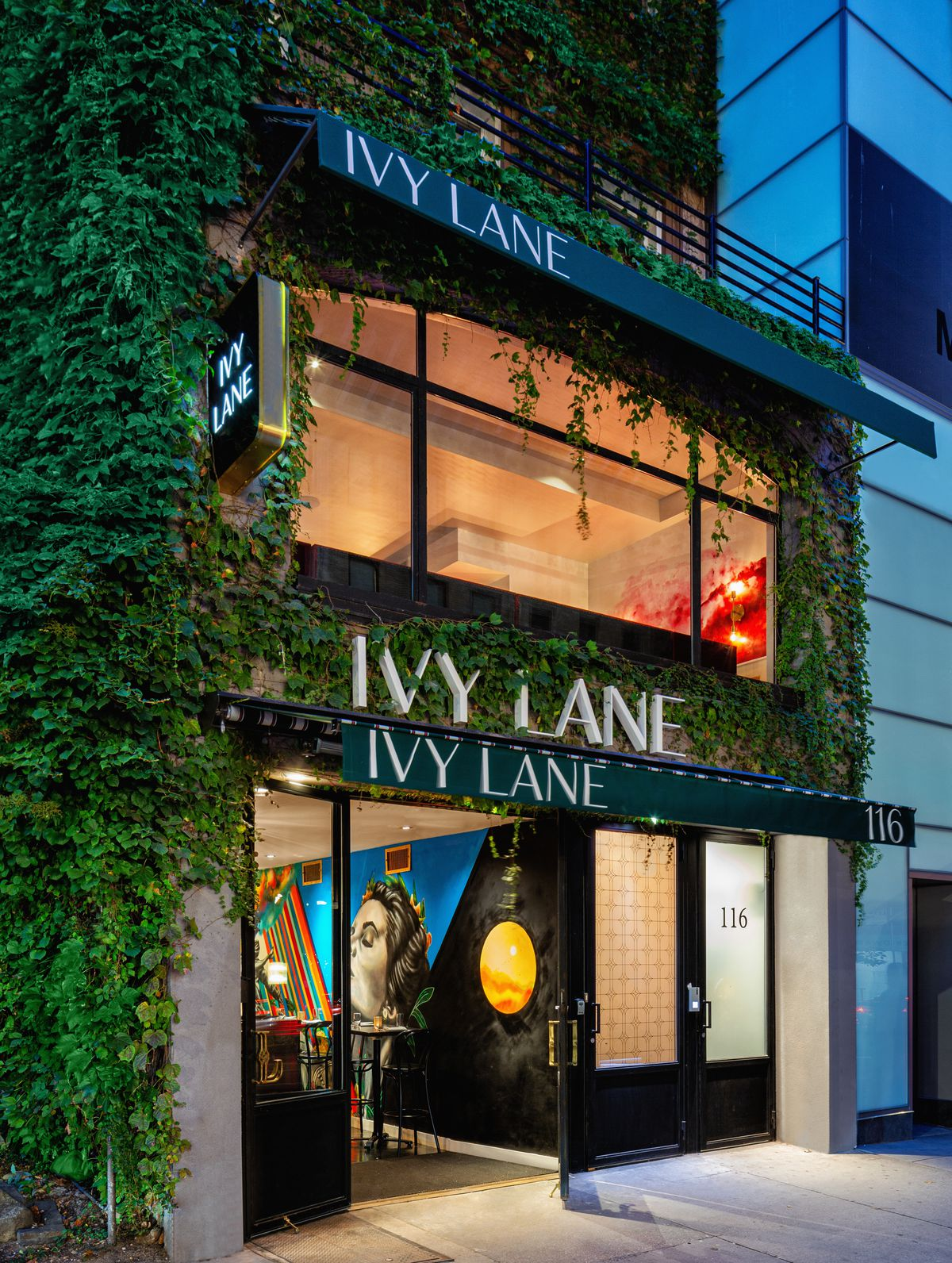 "An exterior of a narrow restaurant with three levels is covered with ivy and has a sign saying ""Ivy Lane"""