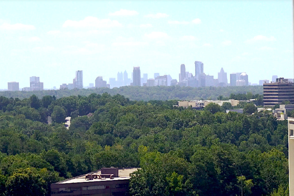 Green treetops and a few mid-rise buildings with the skyscrapers of Atlanta beyond.
