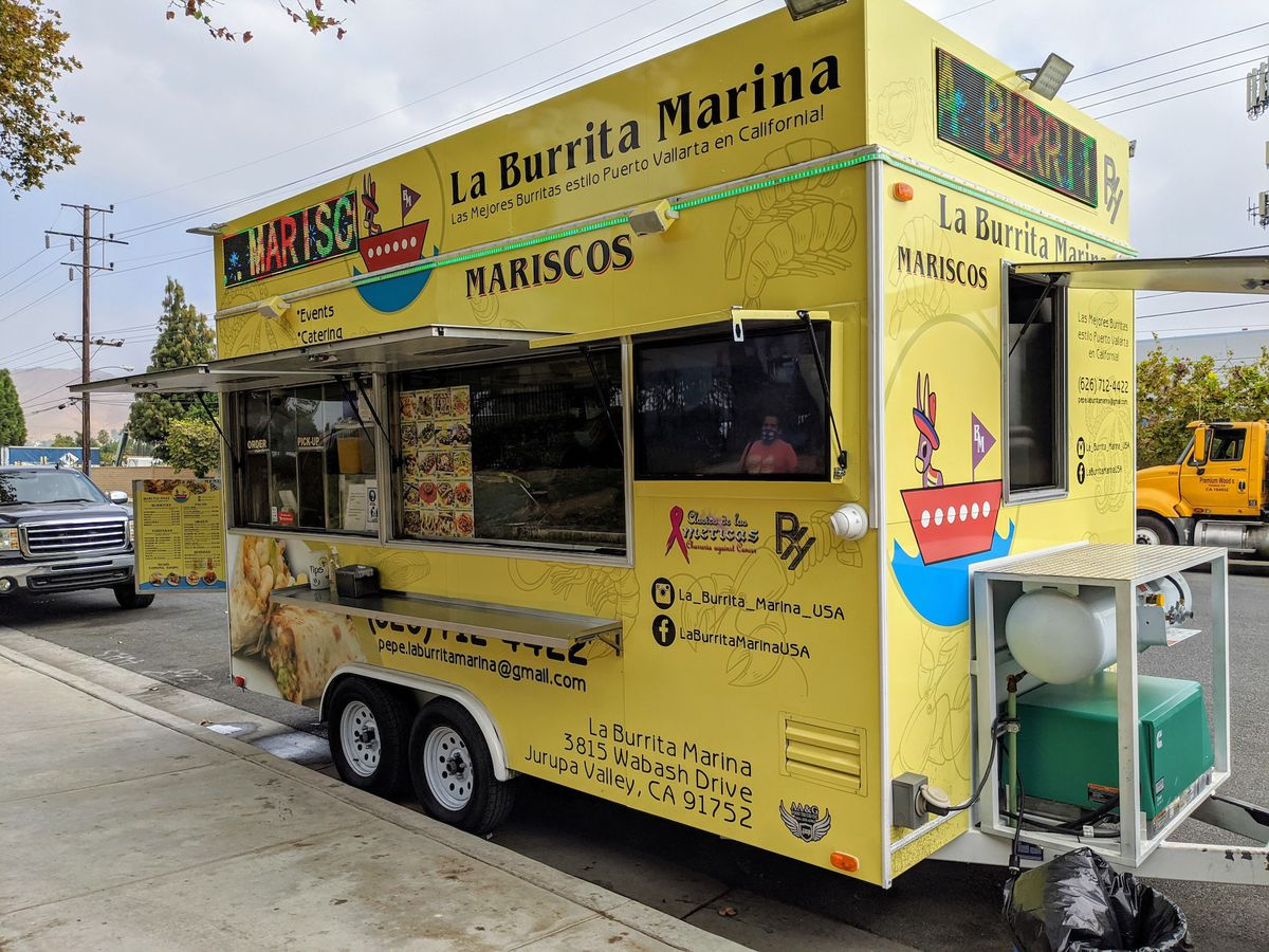 A pale yellow food truck with an open window, selling seafood burritos.