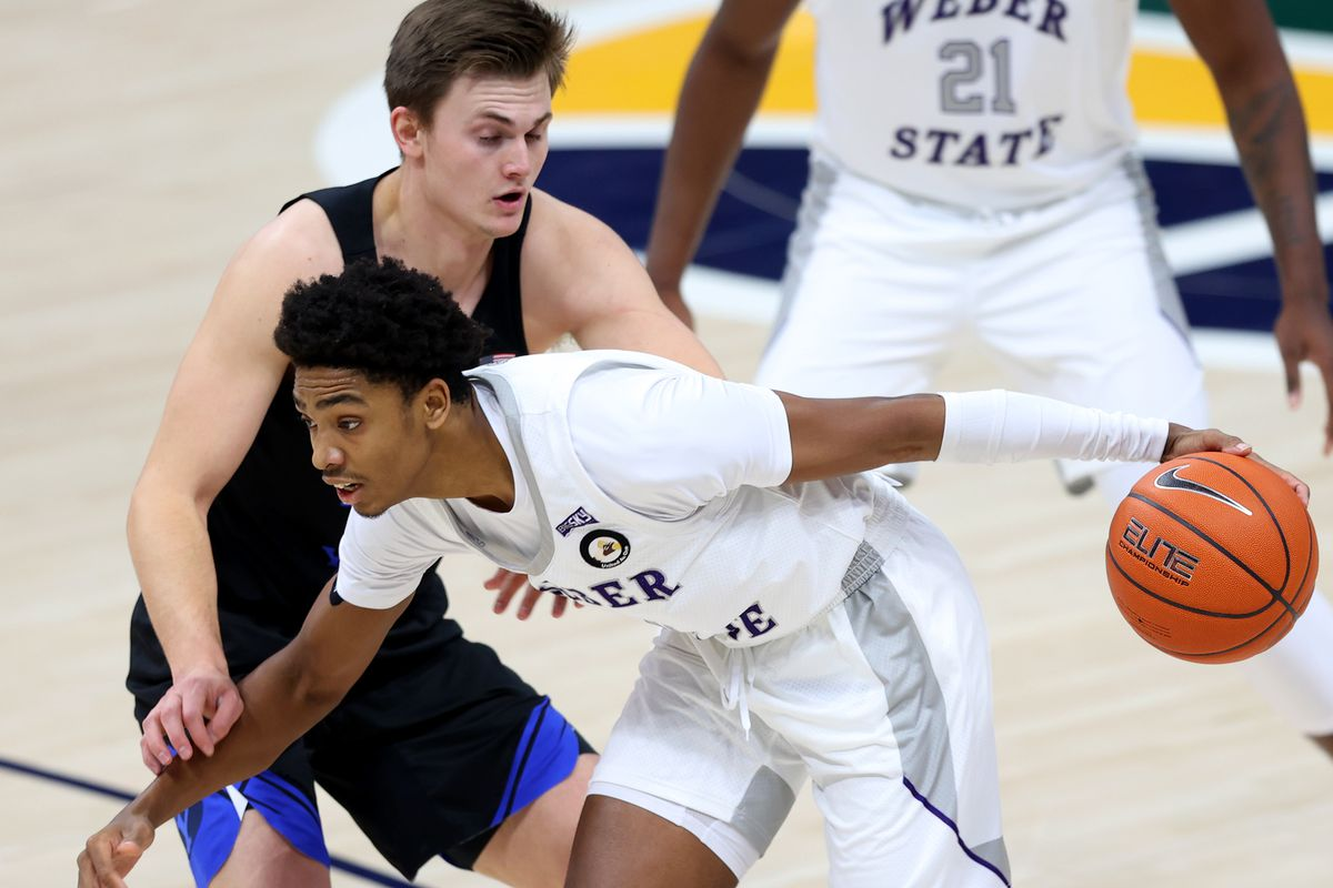 Brigham Young Cougars guard Connor Harding (44) defends Weber State Wildcats guard Zahir Porter (0) as BYU and Weber State play an NCAA basketball game at Vivint Smart Home Arena in Salt Lake City on Wednesday, Dec. 23, 2020.