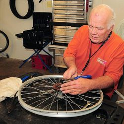 Mike Poling works to free a sprocket from a bent bicycle rim on  Sept. 14, 2012 at the Crossroads Mission bicycle shed in Yuma, Ariz. The sprocket will be cleaned up and used as spare parts on another bike in need of repair. Poling comes to the workshop five days a week to restore donated bikes or part them out to sell or put in reserve for the needy to earn. He'll also take partial bikes and parts to put in his growing stock, and he'll service bikes for a deal.