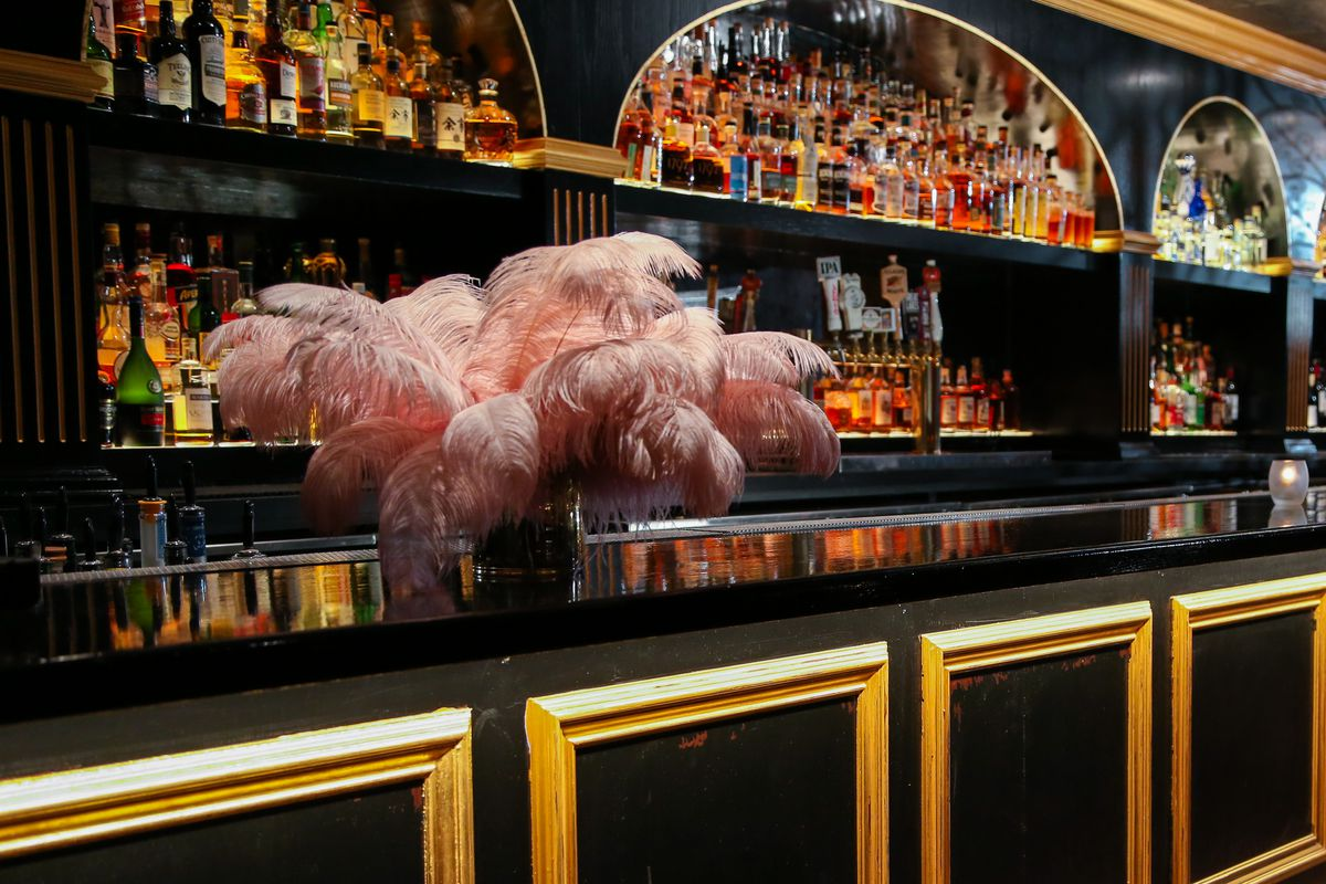 A large black bar with gold accents and a container of big pink feathers.