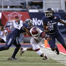 Utah State wide receiver Ron'quavion Tarver (1) avoids a tackle from New Mexico State linebacker Terrill Hanks (2) in the first half of the Arizona Bowl NCAA college football game Friday, Dec. 29, 2017, in Tucson, Ariz. (AP Photo/Rick Scuteri)