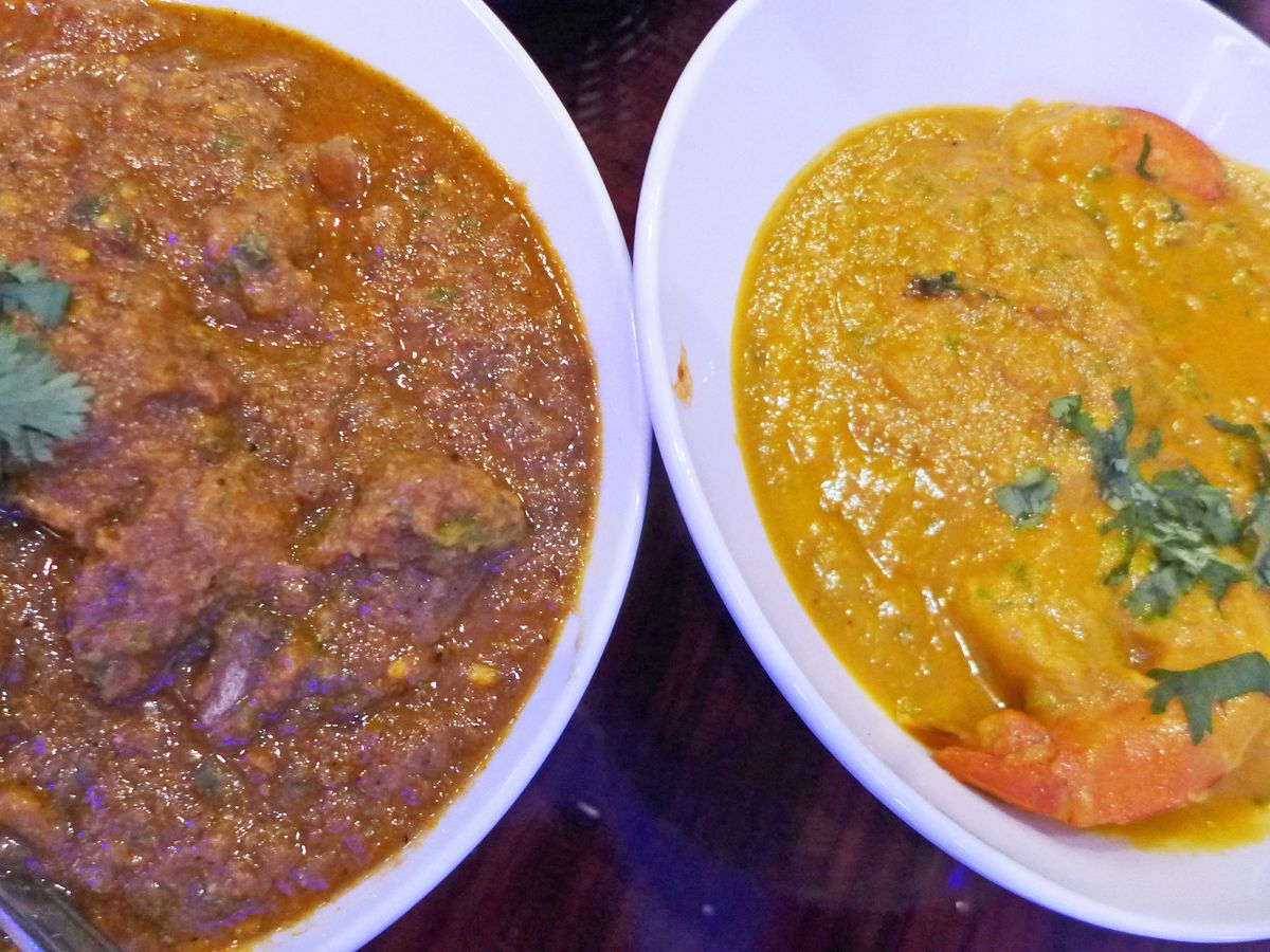 Two bowls of curry, one brown and one yellow, the yellow one with shrimp in it.