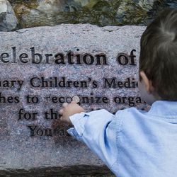 Dash Johnson, 4, a patient at Primary Children's Hospital, and his sister drop a penny on a new plaque during the reopening of the Angel Garden at the hospital in Salt Lake City on Monday, Aug. 1, 2016. The redesigned garden includes more than 1,000 new plants and trees, as well as legacy monuments, including the Butterfly Angel statue, a commissioned 5-foot bronze. Dash's family spearheaded renewal project.