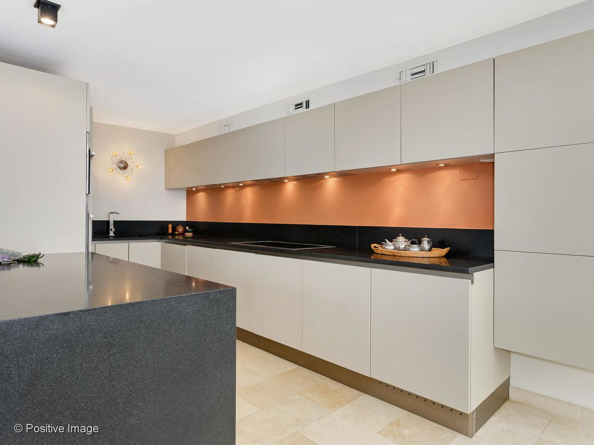 A modern kitchen with clean lines, an orange backsplash, and black countertops. The cabinets are light grey and have minimal hardware.