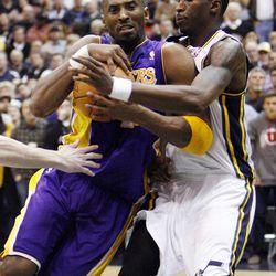 Kobe Bryant, of LA, gets held up by Josh Howard, of Utah, as he drives to the hoop as the Los Angeles Lakers face the Utah Jazz in NBA basketball in Salt Lake City, Wednesday, Jan. 11, 2012.