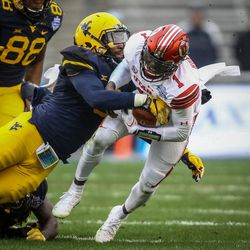 Utah Utes quarterback Tyler Huntley (1) is tackled on a quarter back keeper by West Virginia Mountaineers linebacker Al-Rasheed Benton (3) at the Zaxby's Heart of Dallas Bowl between the Utah Utes and the West Virginia Mountaineers in Dallas Texas on Tuesday, Dec. 26, 2017.