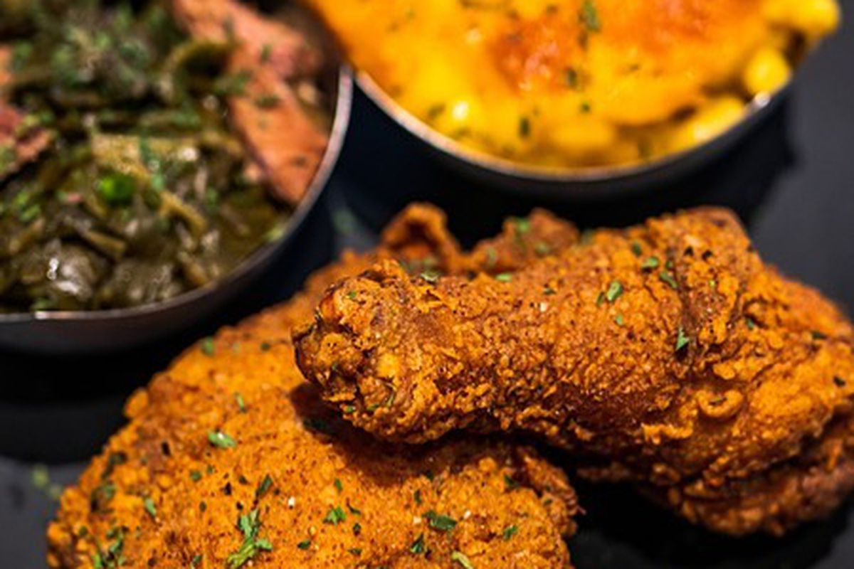 a plate of fried chicken, sauteed greens and baked mac and cheese