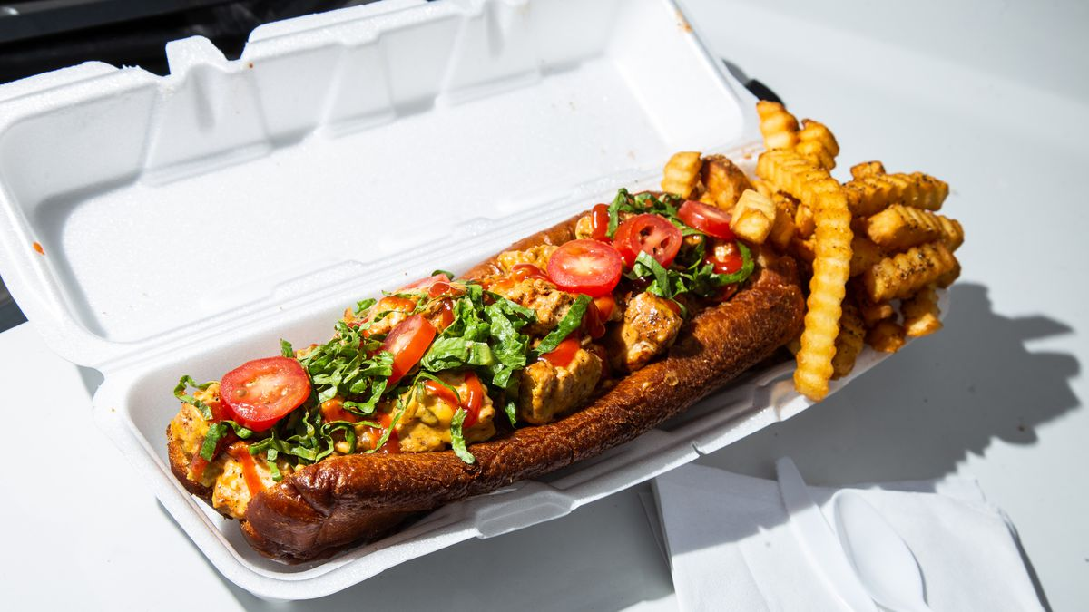 a deep fried chicken cheesesteak with cherry tomatoes, lettuce, special sauce, and crinkle fries in a styrofaum container