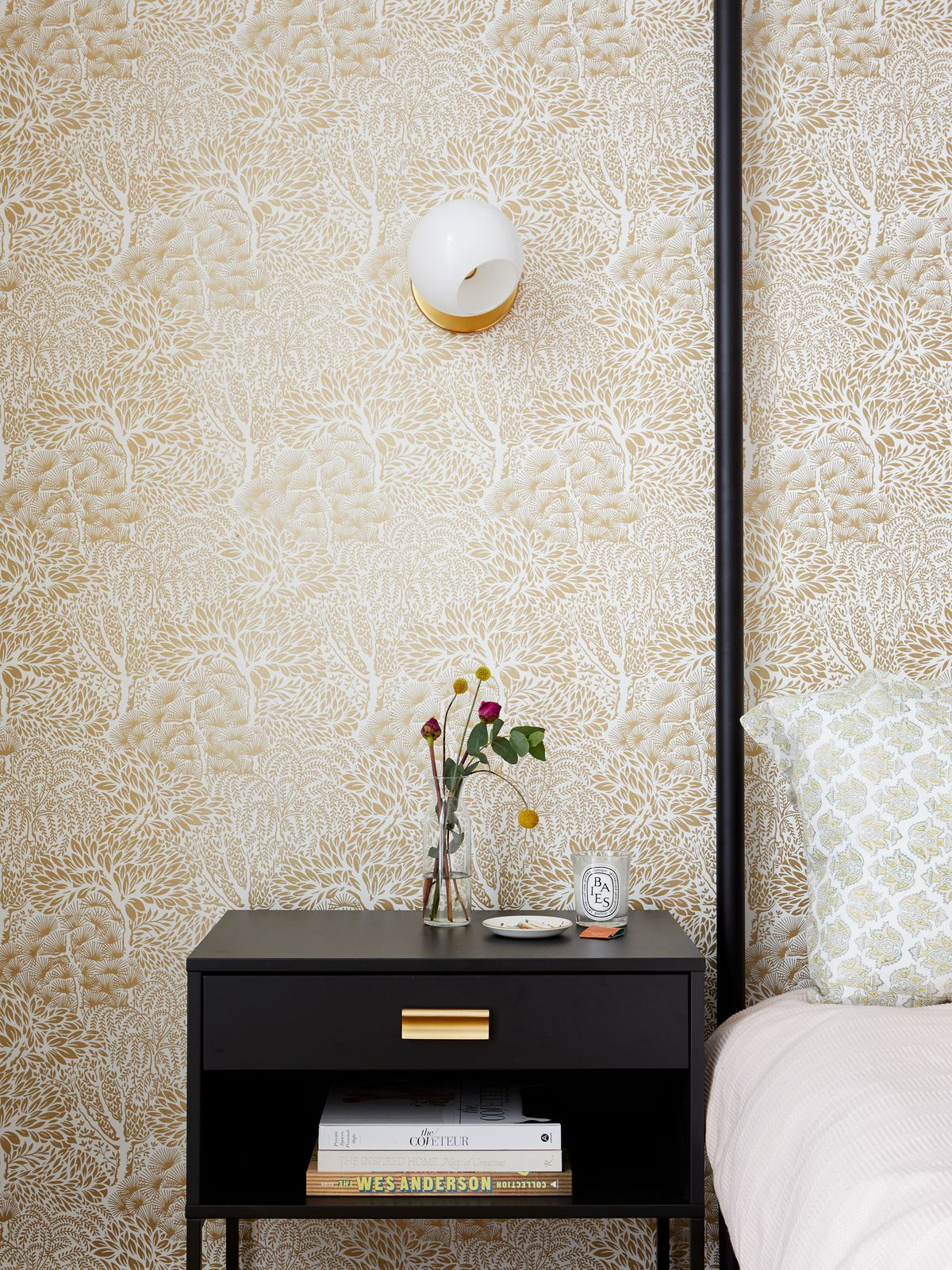 A closely cropped photo of small-scale gold and white wallpaper. In front of the wall sits an elegant black night stand and a portion of a black four-post bed.