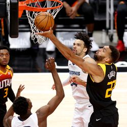 Utah Jazz center Rudy Gobert (27) taps the ball back into to basket with Memphis Grizzlies forward Jaren Jackson Jr. (13) and Memphis Grizzlies forward Dillon Brooks (24) defending him as the Utah Jazz and the Memphis Grizzlies play in game 5 at Vivint Arena in Salt Lake City on Wednesday, June 2, 2021. Utah won 126-110, Utah advances to the second round.