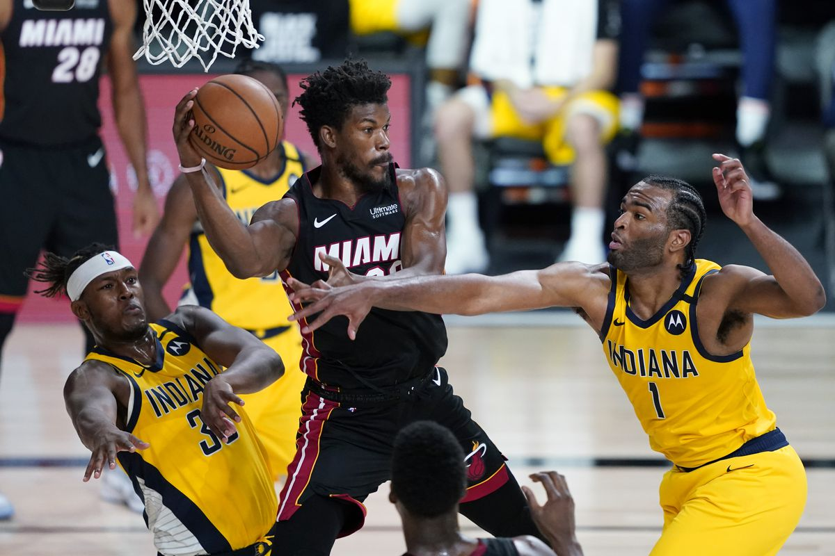 Jimmy Butler of the Miami Heat looks to pass against pressure from Myles Turner and T.J. Warren of the Indiana Pacers during the second half at AdventHealth Arena at ESPN Wide World Of Sports Complex on August 18, 2020 in Lake Buena Vista, Florida.