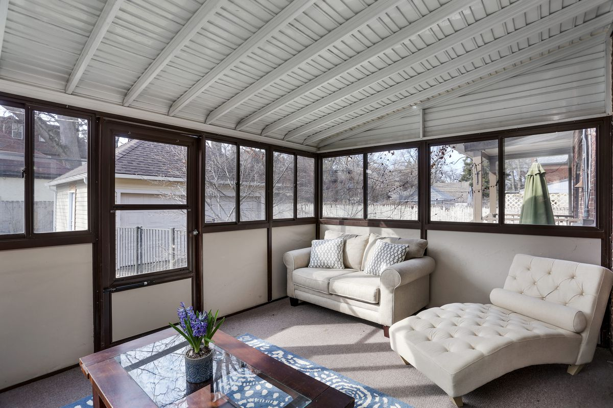 A screened-in porch with a white love seat and lounge. There's a small wooden table.