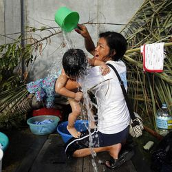 Mildred Villaflores, a member of the Ormoc 2nd Ward, bathes her son Arthur King Villaflores at the chapel, Tuesday, Nov. 19, 2013, in Ormoc, Philippines.