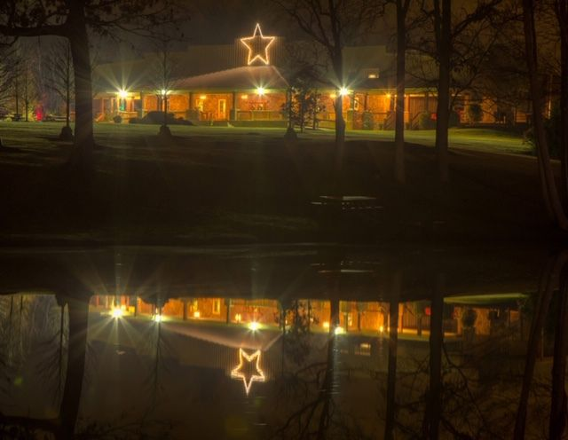 A ranch house at night illuminated with many holiday lights.