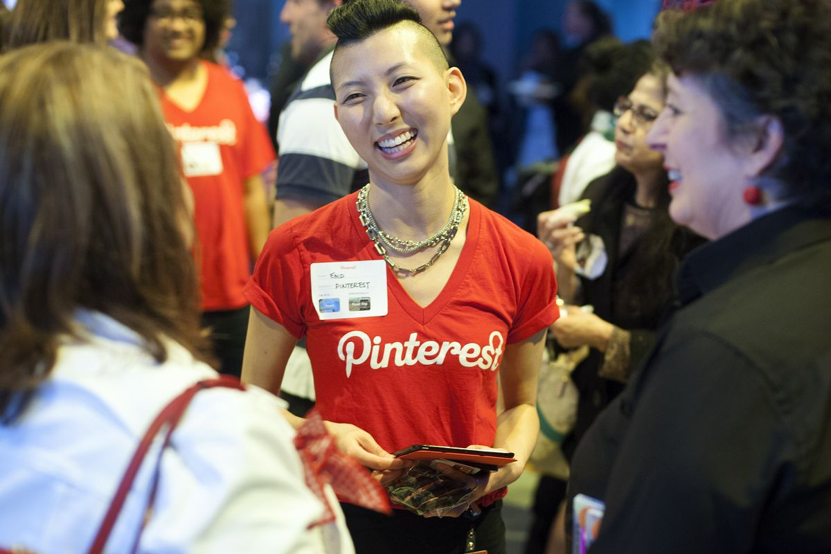 A Pinterest employee in a red Pinterest shirt welcomes guests to the company headquarters for an event.
