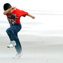 Jayme McFadden, 7, of Havelock, N.C., fights the blowing wind and sand as he plays on Atlantic Beach, N.C., Wednesday.