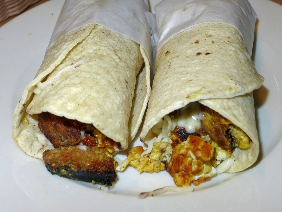 Two rolled flour tortilla tacos with sausage and yellow egg visible at the rolled ends.