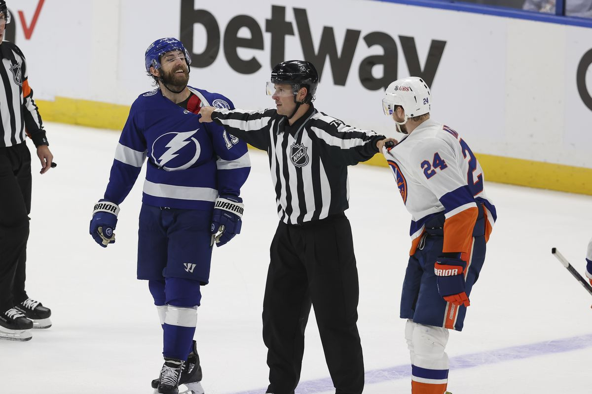 Tampa Bay Lightning right wing Barclay Goodrow (19) is separated from New York Islanders defenseman Scott Mayfield (24) by linesman Kiel Murchison (79) in the third period of Game 5 of the Stanley Cup Playoffs Semifinals between the New York Islanders and Tampa Bay Lightning on June 21, 2021 at Amalie Arena in Tampa, FL.