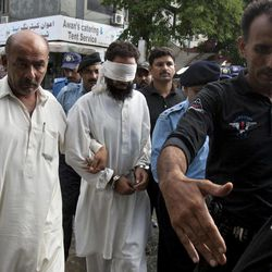 Pakistani police officers escort blindfolded Muslim cleric Khalid Chishti to appear in court in Islamabad, Pakistan, Sunday, Sept. 2, 2012. In the latest twist in a religiously charged case that has focused attention on the country's harsh blasphemy laws, Pakistani police arrested Chishti who they say planted evidence in the case of a Christian girl accused of blasphemy.