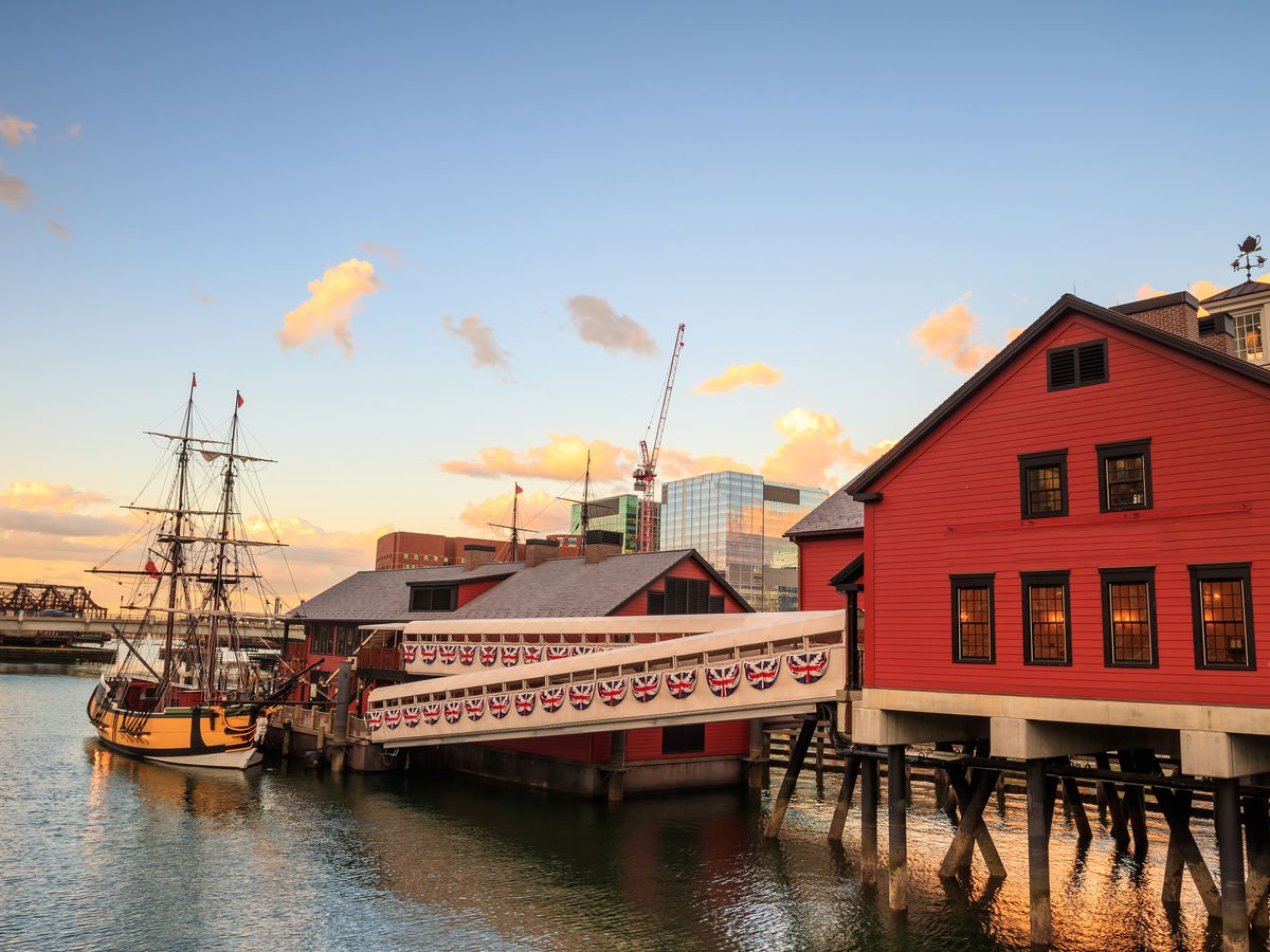 A museum building and dock against a harbor front at twilight.