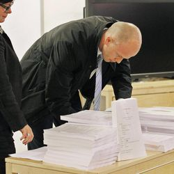 The public prosecutor Svein Holden, right, during the presentation of the second report, of some 300 pages, regarding the mental health of Anders Behring Breivik, stacked onto a table inside the court in Oslo, Norway, Tuesday, April 10, 2012.  According to the new psychiatric assessment report, the right-wing extremist, Anders Breivik, who confessed to killing 77 people in a bomb and shooting rampage in Norway on July 22, 2011, is not criminally insane,  contradicting an earlier assessment.