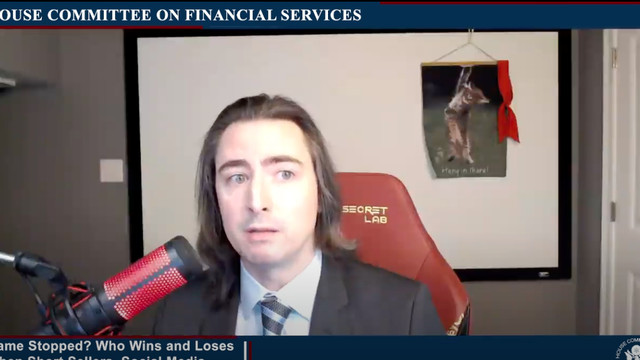 """a man with long hair wearing a jacket and tie and speaking into a microphone looks off camera as he speaks. on the wall behind him is the meme poster """"hang in there"""" showing a kitten dangling from a branch"""