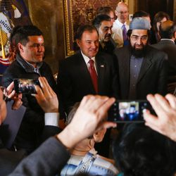 Gov. Gary Herbert poses for pictures after signing a concurrent resolution affirming Utah's support for the religious and civil liberties of immigrants and refugees during a ceremony at the Capitol in Salt Lake City on Monday, April 17, 2017.
