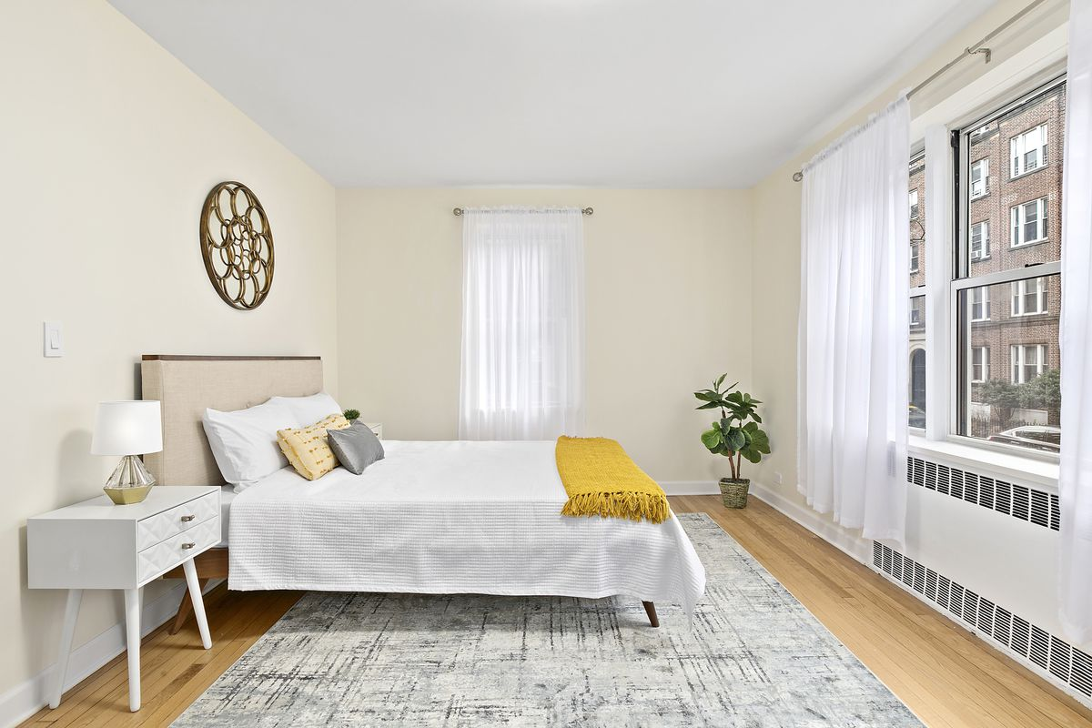 A bedroom with a small bed, beige walls, a large window, and hardwood floors.
