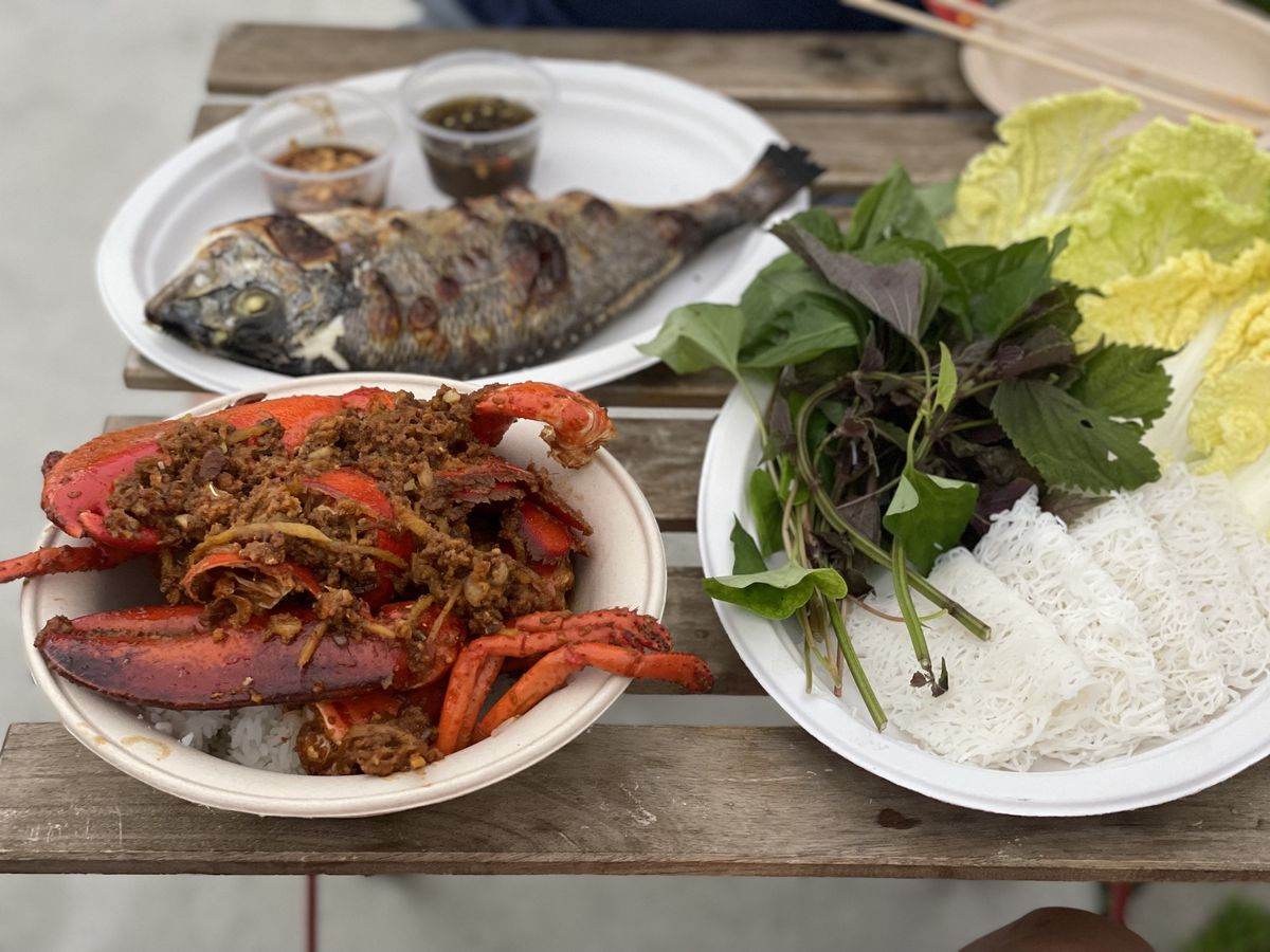 Plates of lobster, grilled fish, and herbs