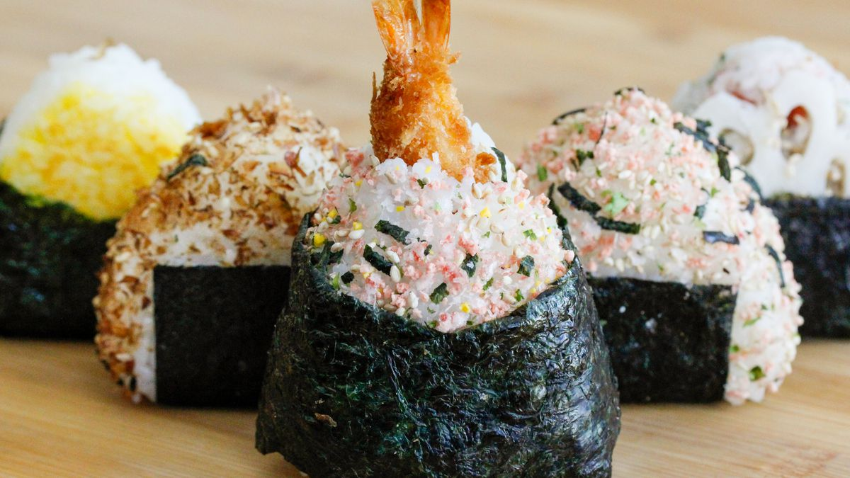 Triangle-shaped onigiri (rice balls) wrapped in nori. The rice is studded with spices, and one rice ball has a shrimp tail sticking out.