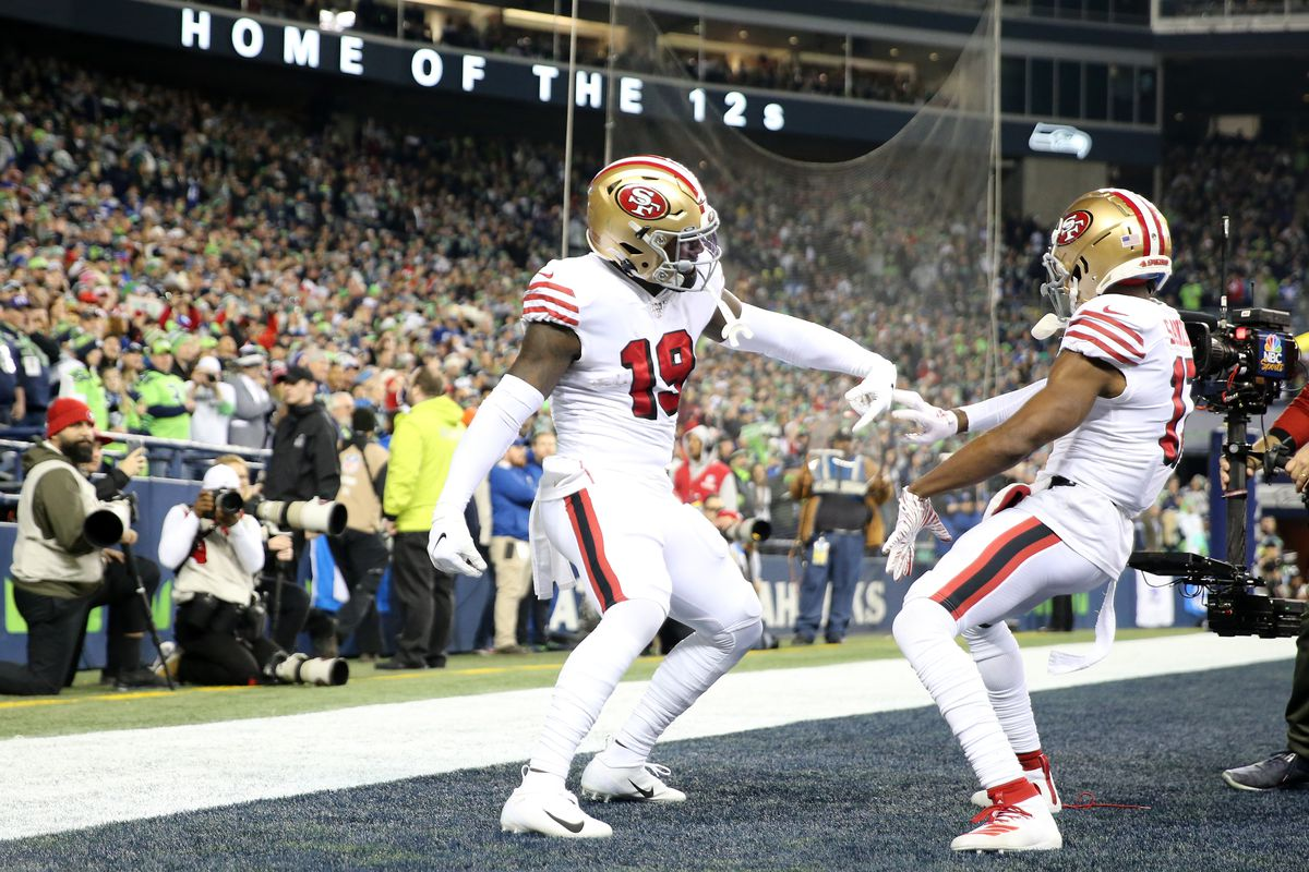 Wide receiver Deebo Samuel of the San Francisco 49ers celebrates his touchdown with teammate wide receiver Emmanuel Sanders against the Seattle Seahawks during the first quarter of the game at CenturyLink Field on December 29, 2019 in Seattle, Washington.
