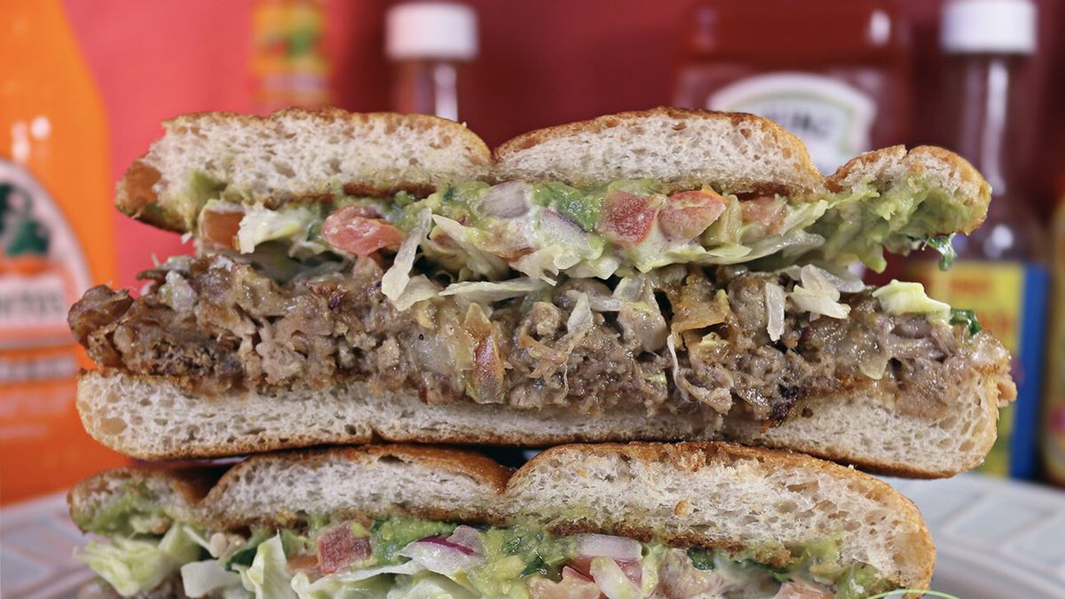 Closeup cross-section of a Mexican torta, with meat, guacamole, and more sandwiched between bread