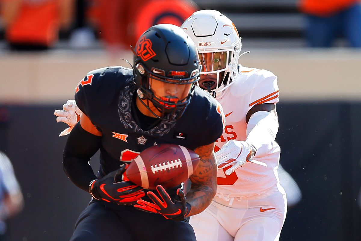Wide receiver Tylan Wallace of the Oklahoma State Cowboys catches an 11-yard touchdown pass against defensive back Josh Thompson of the Texas Longhorns in the first quarter at Boone Pickens Stadium on October 31, 2020 in Stillwater, Oklahoma.