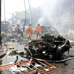 Thai fire fighters walk near a wreckage of a car while others trying to put off fire at a building after the car bomb blasted in Yala, southern Thailand, Saturday, March 31, 2012.