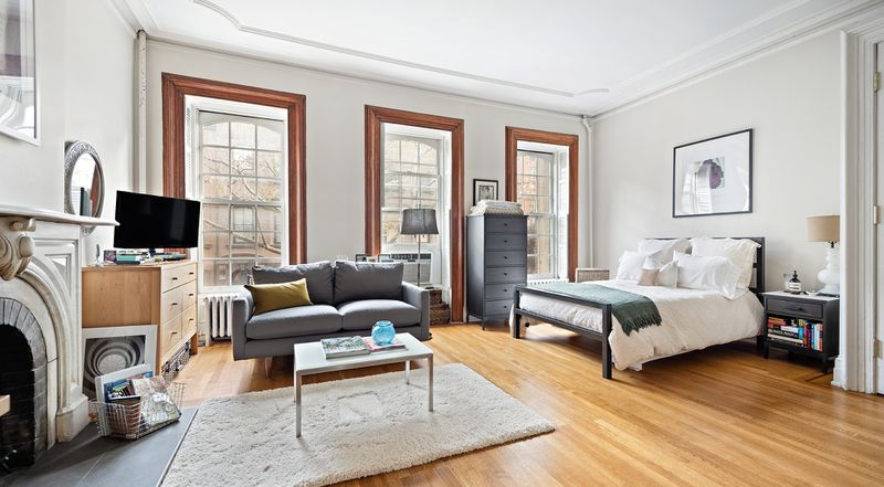 A bedroom with hardwood floors, three large windows, a fireplace, and decorative moldings.