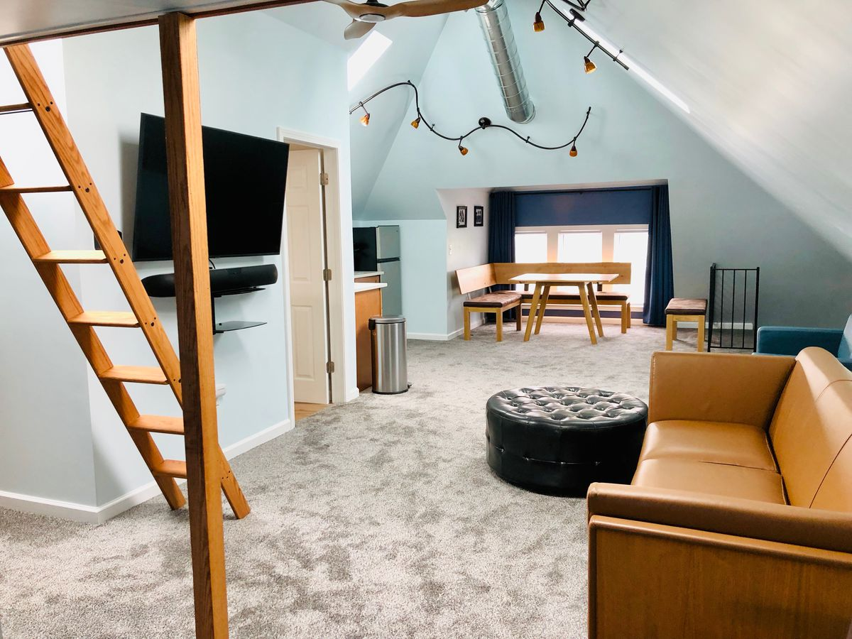 A carpeted room with light blue walls and a brown couch. A ladder lead to a little lofted space.