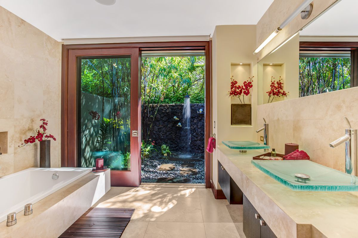 A beige bathroom has two glass sinks, a tub, and an outdoor shower.