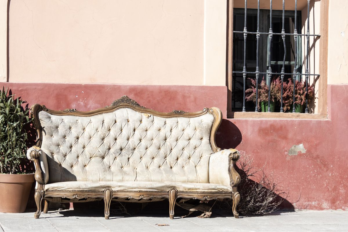 An old beat-up sofa on the sidewalk