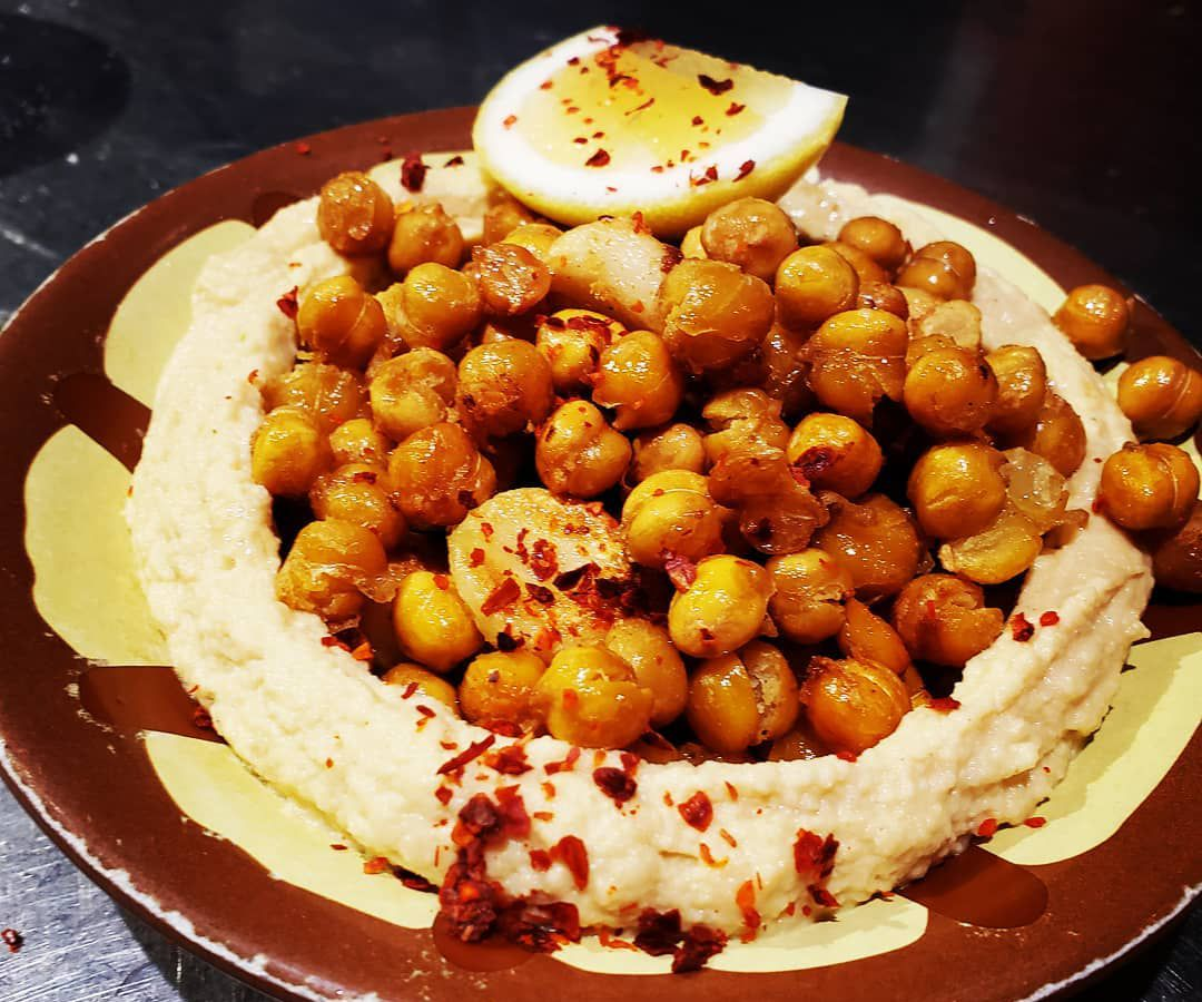 A plate with hummus with pine nuts and garlic at Cafe Munir.